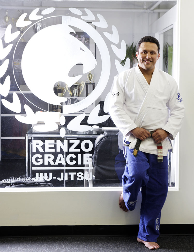 Renzo Gracie leaning against a glass wall in his office